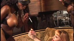 Une esclave sexuelle blonde lèchent les vagins et les nichons de deux maitresses noires